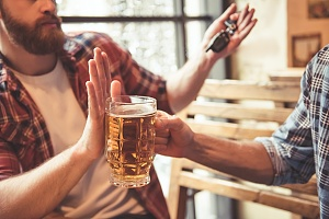 a wingman preventing a recovering addict from drinking at a social event