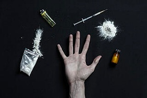 various drugs with a hand a lighter which are items an addict would use