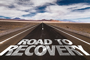 a long view of a road with the words road to recovery on the ground