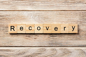 the word recovery spelled out with scrabble letters on a table