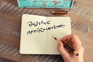 the words positive affirmation written in a notebook on a table
