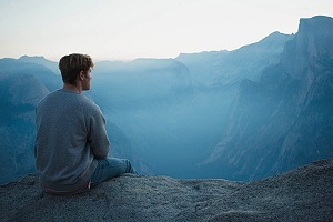 a man meditating on a mountain ledge to avoid relapsing on his alcohol recovery journey