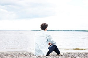 man sitting on a beach contemplating how to deal with his co-occuring disorder