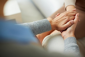 a therapist holding the hands of a patient who is receiving addiction support services