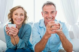 a man and woman holding mugs smiling while drinking at home