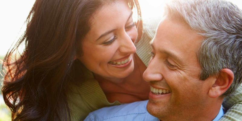 A woman and man smiling at each other in the sunlight