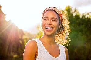 a woman smiling in the sunlight outside