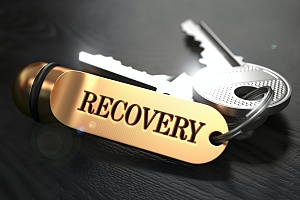 silver keys on a gold keychain that says recovery