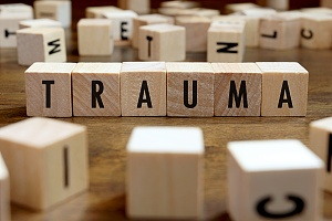 the word trauma spelled out with wooden blocks