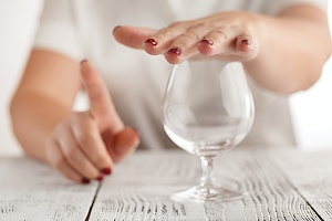 woman with her finger up and and her hand over a glass representing abstinence from drinking in an intensive outpatient program