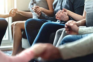peer support shown by people holding hands in a circle