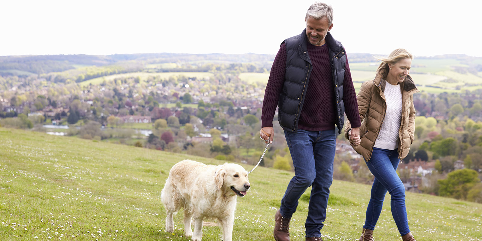 man and wife walking their dog after learning what Integrated Behavioral Model is