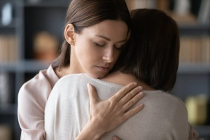 women giving a hug to someone with early signs of addiction