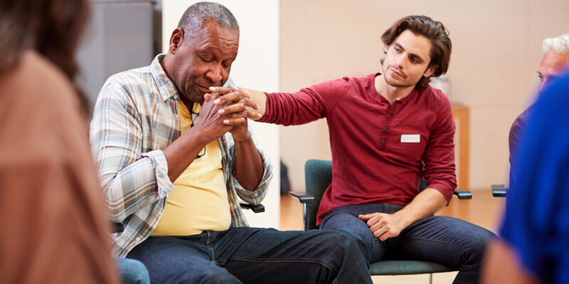 men comforting another in substance abuse group therapy activities