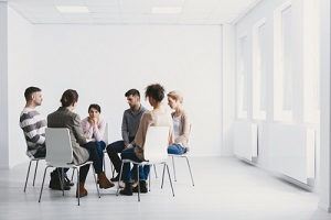 Group Psychotherapy in White Interior during substance abuse group therapy activity