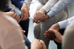 People Holding Hands during substance abuse group therapy activity