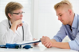 doctor talking to her male patient at office about Outpatient Drug Treatment Programs