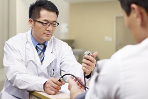 asian doctor measuring blood pressure of a patient