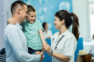 nurse holding hands and communicating with small boy